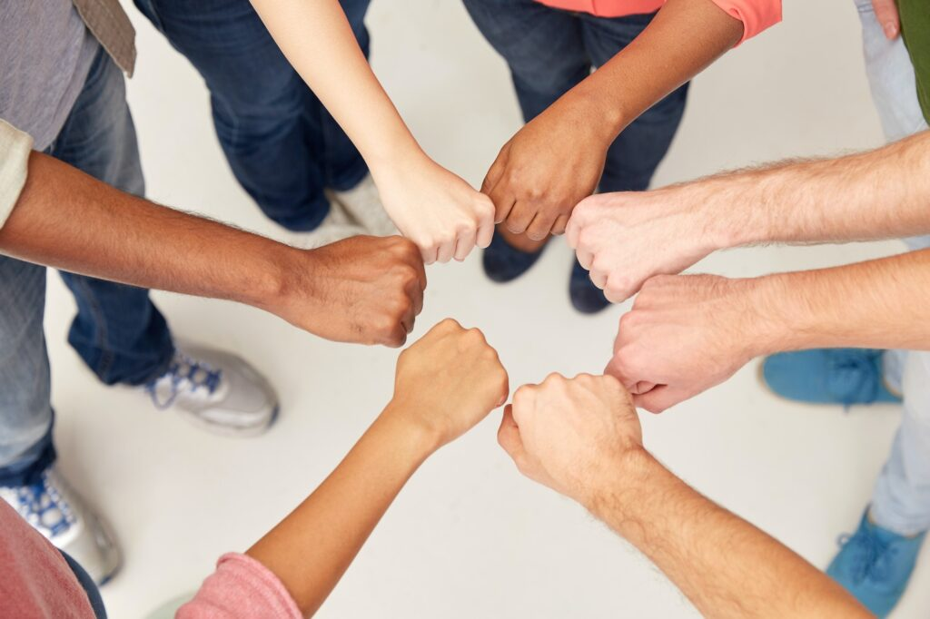 hands of international people making fist bump